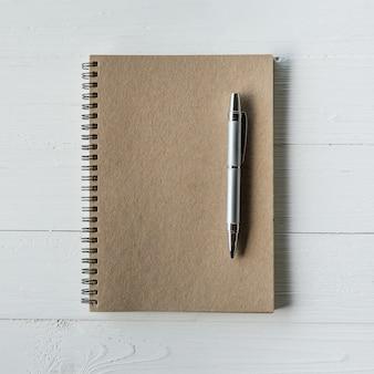 Bruin boek en pen op witte houten tafel