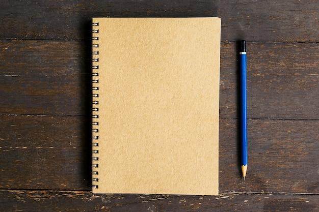 Bruin boek en potlood op houten lijstachtergrond met ruimte