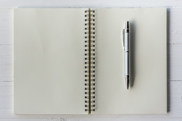 Bruin boek open en pen op witte houten tafel