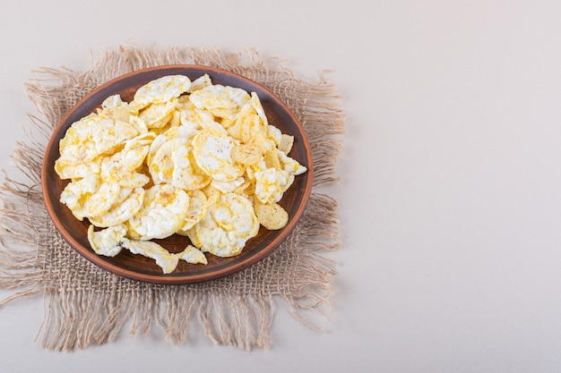 Bruin bord met knapperige rijstchips op witte tafel
