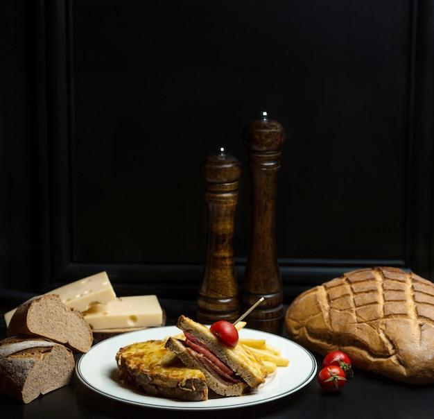 Bruin broodsandwich met gekookte ham en geraspte kaas