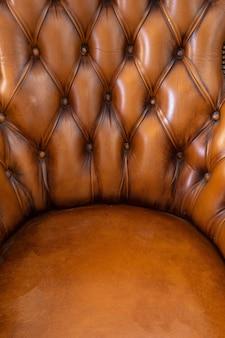 Bruin chesterfield stijl lederen abstracte textuur als achtergrond, fauteuil close-up modern design