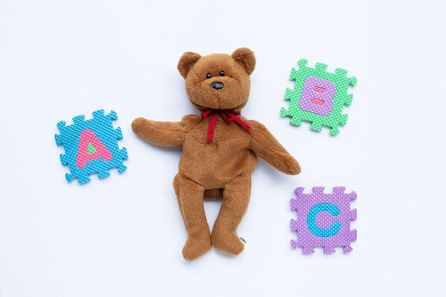 Bruin draag stuk speelgoed met engels het onderwijsconcept van het alfabetraadsel.