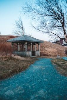 Bruin en wit blokhuis dichtbij naakte bomen onder blauwe hemel overdag