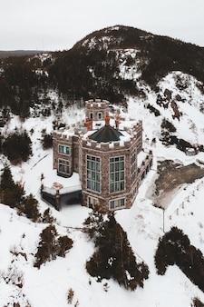 Bruin en wit huis op sneeuw behandelde grond