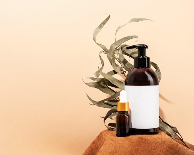 Bruin flessenmodel voor natuurlijke cosmetica-spa-accessoires op bruin lederen podiumcrèmeachtergrond en bladeren