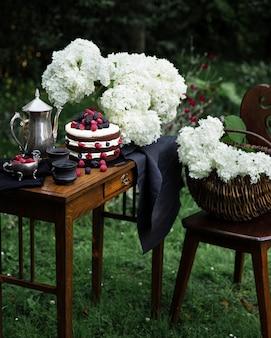 Bruin fruitcake op de houten smalle tafel in de tuin. zilveren theepot en twee zwarte kopjes thee complementeren de compositie.