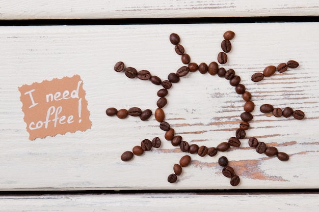 Bruin gebrande koffiebonen gerangschikt in een vorm van zon. ik heb koffie nodig. wit houten oppervlak.