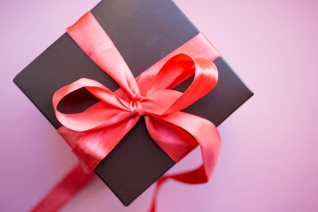 Bruin geschenkdoos met rood lint op roze achtergrond. bovenaanzicht met kopie ruimte.