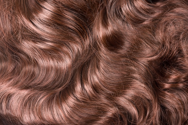 Bruin haar textuur. golvend lang krullend lichtbruin haar close-up als achtergrond. hair extensions, materialen en cosmetica, haarverzorging. kapsel, kapsel of sterven in salon.