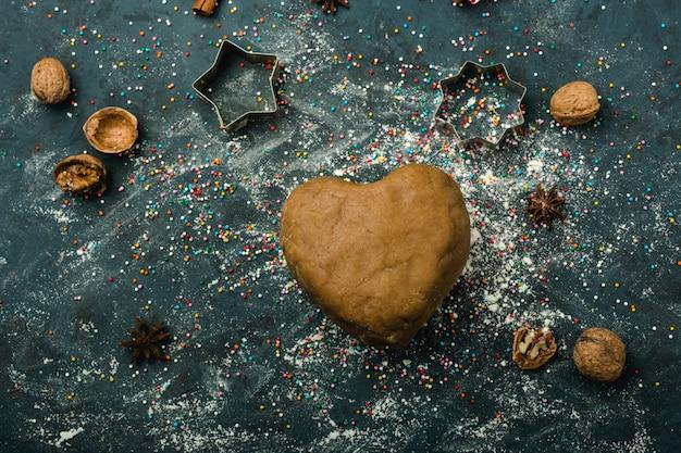 Bruin het deeg in de vorm van een hart op tafel, bestuif met bloem, bovenaanzicht, donkerblauwe achtergrond. vakantie inhoud