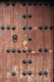 Bruin houten antieke deur met metalen klinknagels en deurklopper