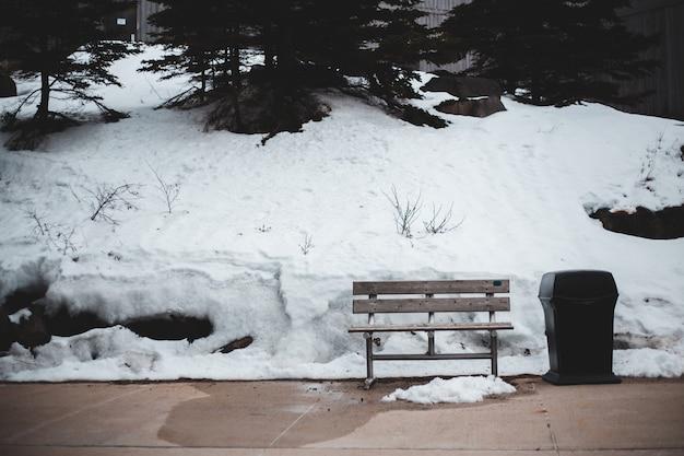 Bruin houten bankje op besneeuwde grond