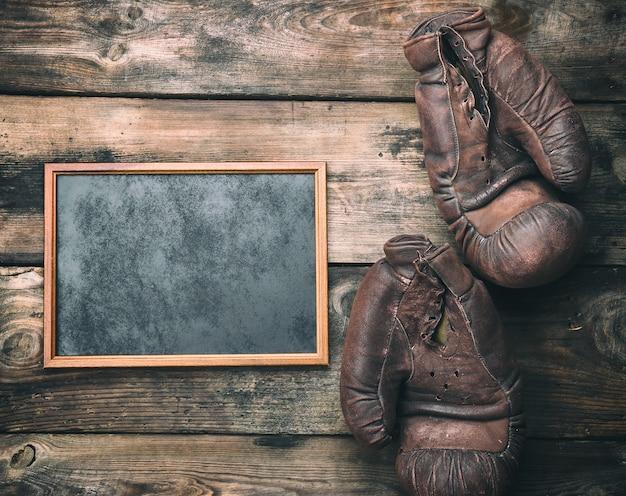Bruin houten frame en zeer oude lederen bokshandschoenen