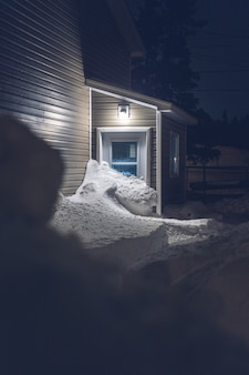 Bruin houten huis bedekt met sneeuw tijdens de nacht