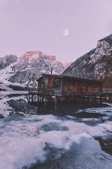 Bruin houten huis in de buurt van besneeuwde berg