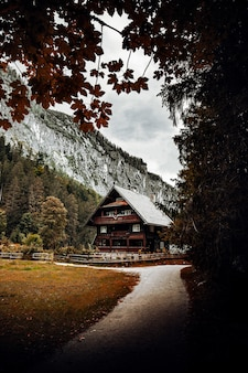 Bruin houten huis in de buurt van groene bomen en bergen overdag