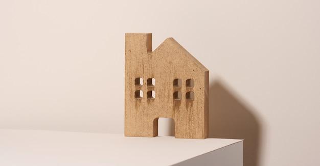 Bruin houten huis op een beige achtergrond. vastgoed verhuur, aankoop en verkoop concept. makelaarsdiensten, reparatie en onderhoud van gebouwen
