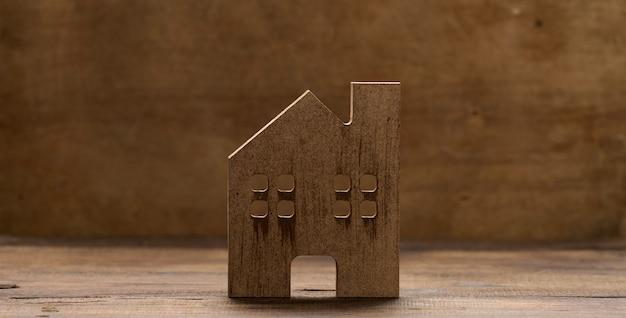 Bruin houten huis op een bruine achtergrond. vastgoed verhuur, aankoop en verkoop concept. makelaarsdiensten, reparatie en onderhoud van gebouwen, kopieerruimte