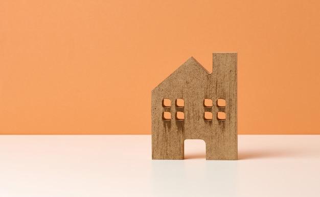 Bruin houten huis op een oranje achtergrond. vastgoed verhuur, aankoop en verkoop concept. makelaarsdiensten, reparatie en onderhoud van gebouwen, kopieerruimte