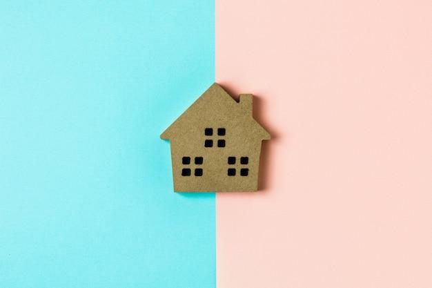 Bruin houten huispictogram op blauwe en roze achtergrond