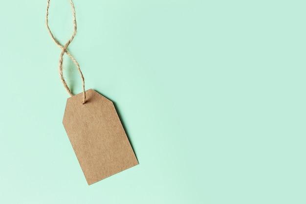 Bruin kartonnen prijskaartje op pastel groen, bovenaanzicht. verkoop ondertekenen.