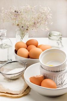 Bruin kippeneieren in een kom en eierschaal in een kom met bloem en zeef op papier