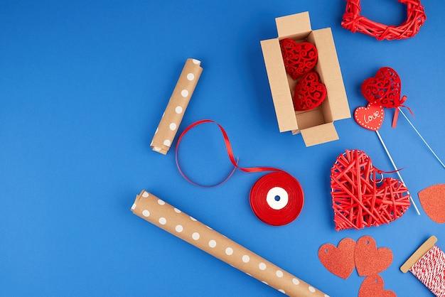Bruin kraftpapier, geschenkverpakking, rood lint, rood hart, set items voor het maken van geschenken met uw eigen handen. geschenkverpakking