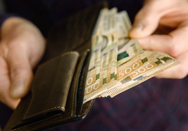 Bruin lederen portemonnee met bankbiljetten op oude houten oppervlak