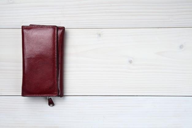 Bruin lederen portemonnee op een witte houten tafel