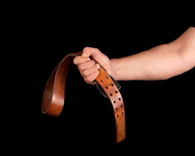Bruin lederen riem met een ijzeren gesp in de hand van een man