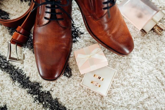 Bruin lederen schoenen, riem, parfum en gouden ringen.