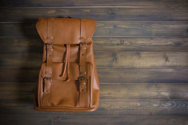 Bruin lederen tas op houten tafel. bovenaanzicht. reis concept.