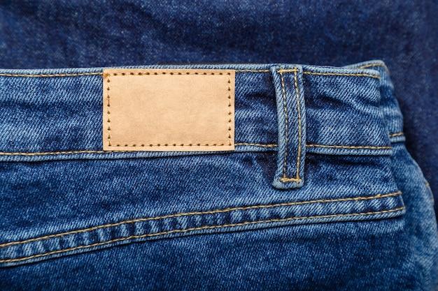 Bruin leeg etiket, leermarkering op de achtergrond van de denimbroek. leeg mockup beige lederen label. blauwe denim jeans met emty label. detailopname.