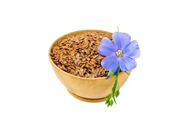Bruin lijnzaad in houten kom met blauwe bloem geïsoleerd op een witte achtergrond
