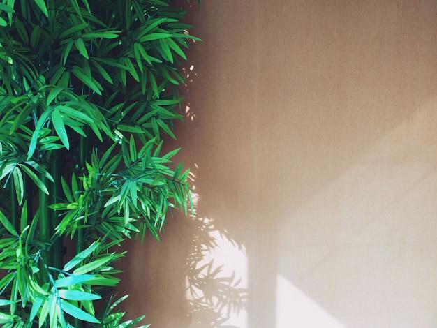 Bruin muurbinnenland met bamboeinstallatie, de natuurlijke binnenlandse achtergrond van het ontwerpconcept