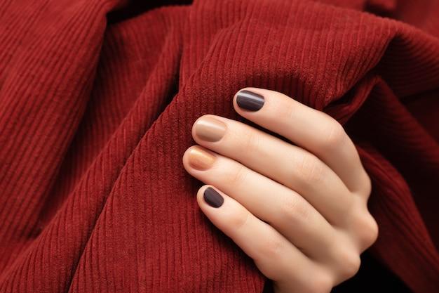 Bruin nageldesign. vrouwelijke hand met glitter manicure.