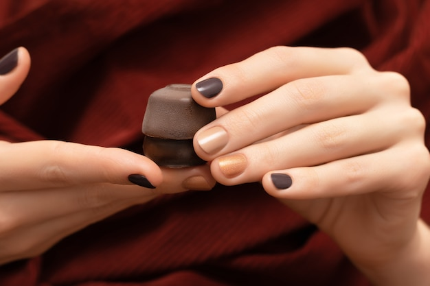 Bruin nageldesign. vrouwelijke handen die chocoladesuikergoed houden.