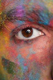 Bruin oog van de jonge mens met heldere kleurrijke verf