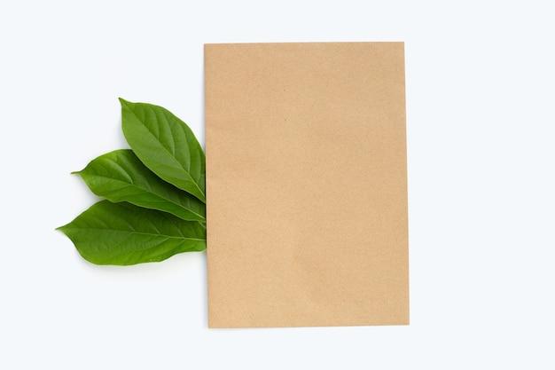 Bruin papier met groene bladeren op wit