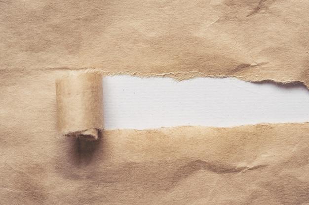 Bruin papier wordt gescheurd om een wit paneel voor tekst te onthullen