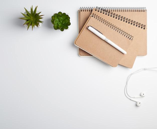 Bruin spiraalvormig notitieboekje met lege bladen, pen en groene installaties in een pot