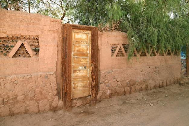 Bruine adobe buitenmuur met houten deur en groen gebladerte in een stad in het noorden van chili