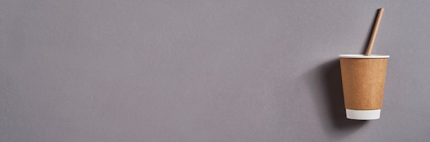 Bruine afhaalkoffiemok met papieren rietje op grijze trendkleurtabel. zero waste, duurzaam levensstijlconcept. bovenaanzicht met kopie ruimte