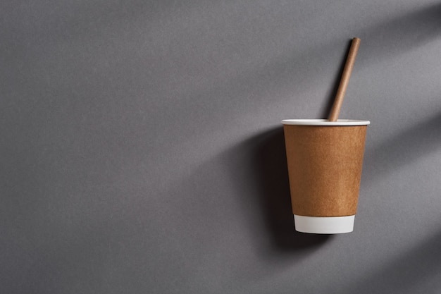 Bruine afhaalmaaltijden koffiemok met papier rietje met diepe schaduwen uit het raam op grijze trendkleur achtergrond. geen afvalconcept. bovenaanzicht.