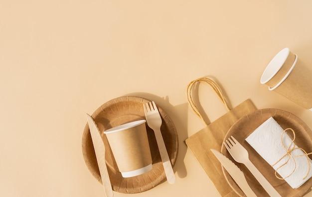 Bruine ambachtelijke wegwerpzak en tafelgerei beker, plaat en houten vork, mes op bruin oppervlak plat lag bovenaanzicht