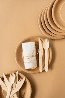 Bruine ambachtelijke wegwerpzak en tafelgerei beker, plaat en houten vork, mes op bruin oppervlak