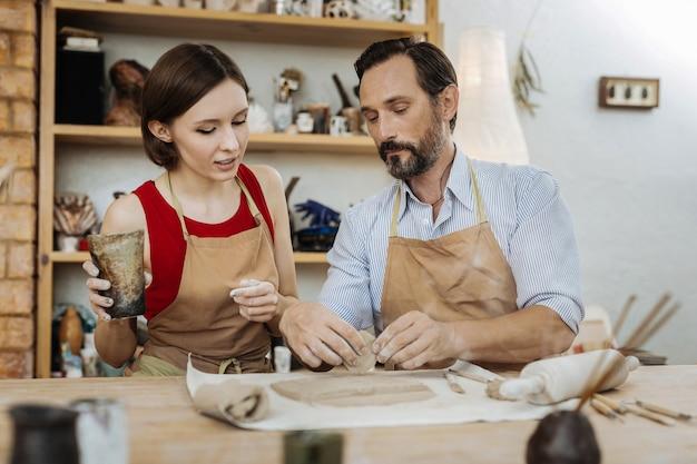 Bruine bekers. een stel pottenbakkers geniet enorm van hun werk tijdens het maken van mooie bruine kopjes