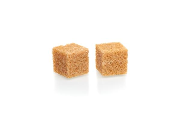 Bruine blokjes rietsuiker geïsoleerd op een witte achtergrond. close-up bekijken.