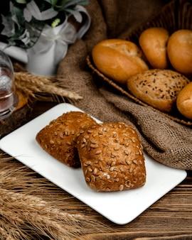 Bruine broodjes met zonnebloempitten bovenop